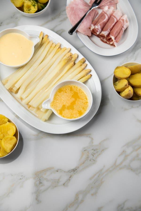 Asparago tedesco bianco del vassoio con il prosciutto cucinato ed affumicato delle patate, il Hollandaise della salsa ed il burro fotografia stock