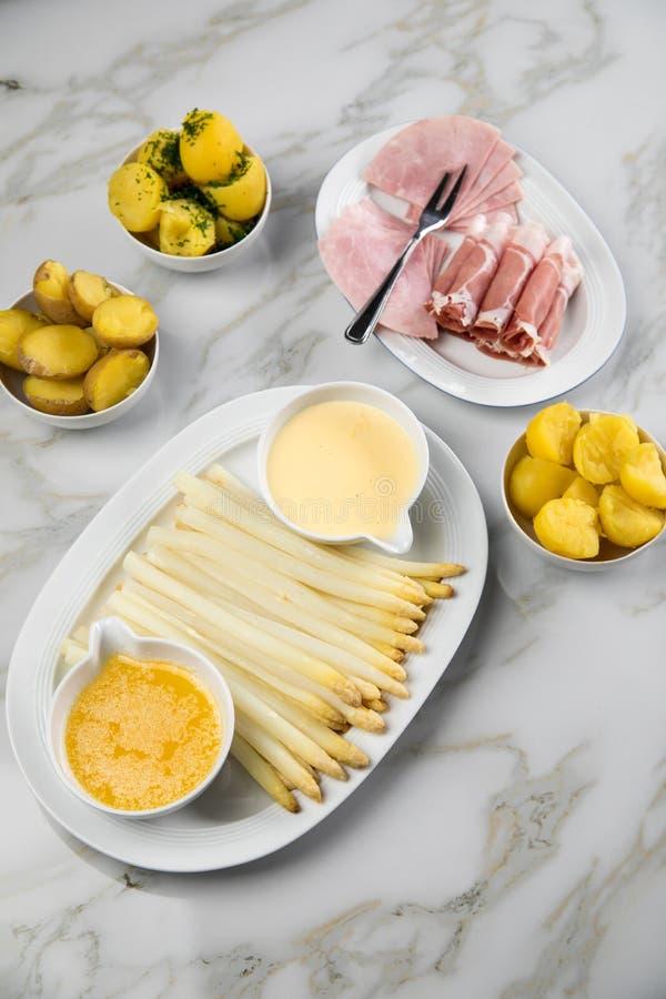 Asparago tedesco bianco del vassoio con il prosciutto cucinato ed affumicato delle patate, il Hollandaise della salsa ed il burro immagine stock libera da diritti