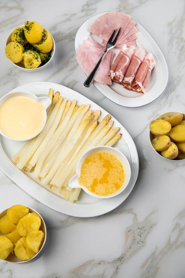 Asparago tedesco bianco del vassoio con il prosciutto cucinato ed affumicato delle patate, il Hollandaise della salsa ed il burro fotografie stock