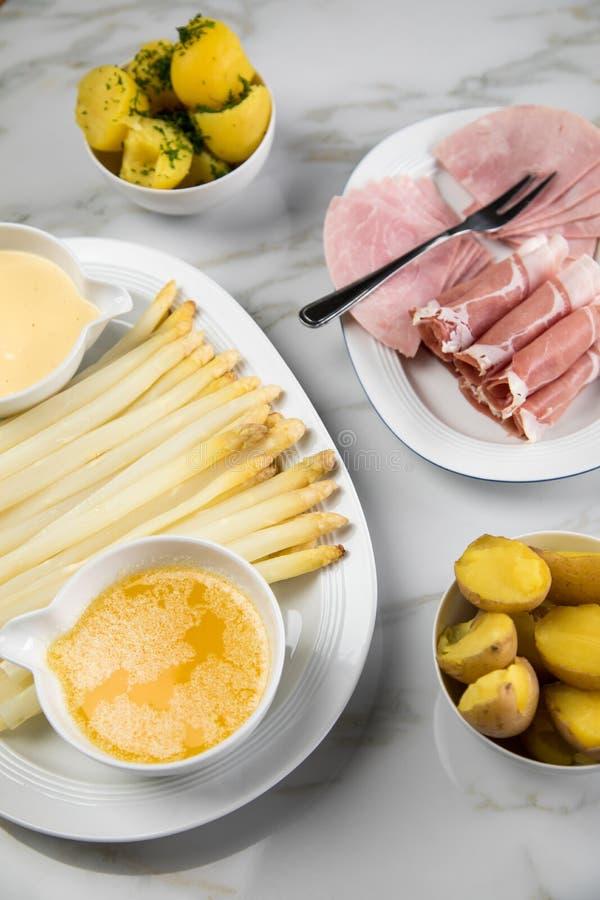 Asparago tedesco bianco del vassoio con il prosciutto cucinato ed affumicato delle patate, il Hollandaise della salsa ed il burro fotografia stock libera da diritti