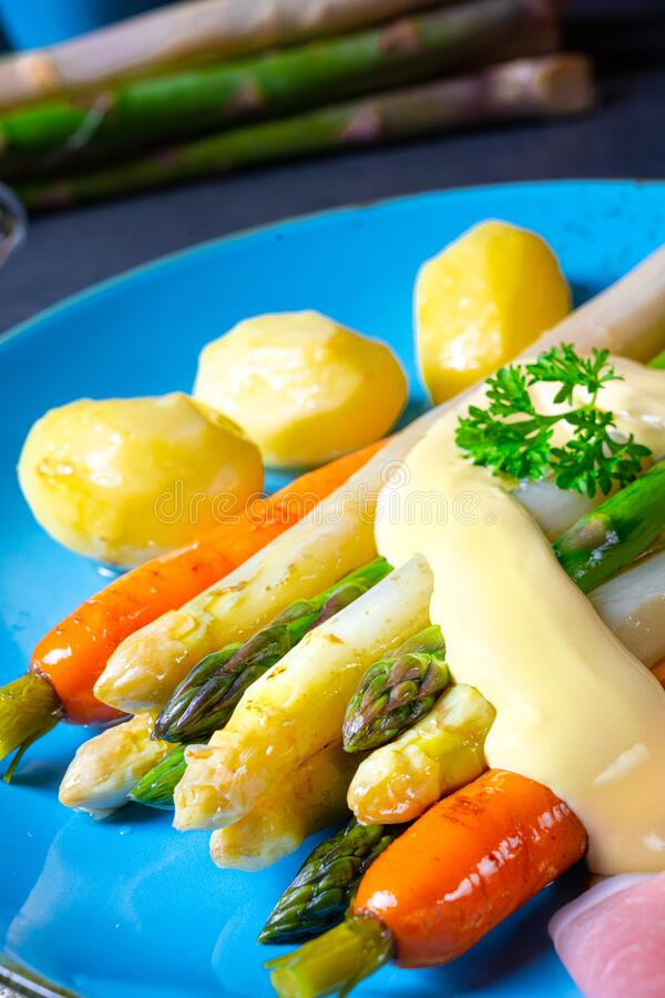 Asparagus with black forest ham, carrots and hollandaise sauce royalty free stock photography