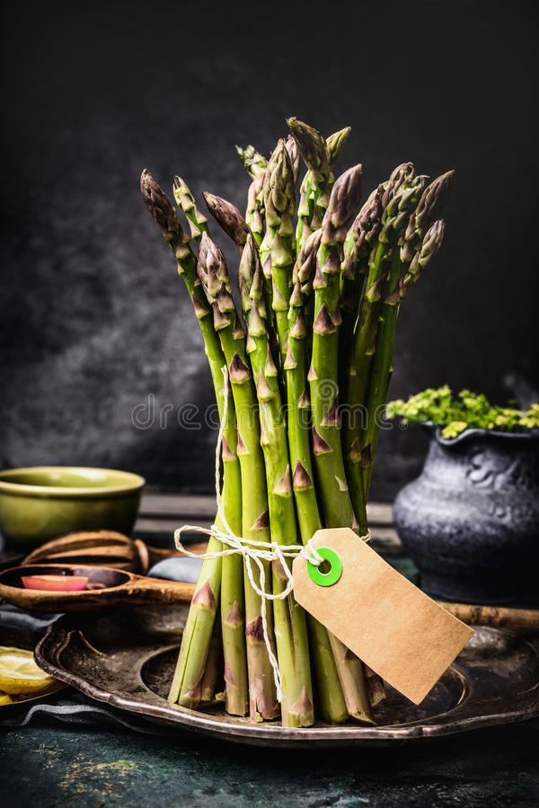 Asparagus bunch with blank tag on dark rustic kitchen table royalty free stock images