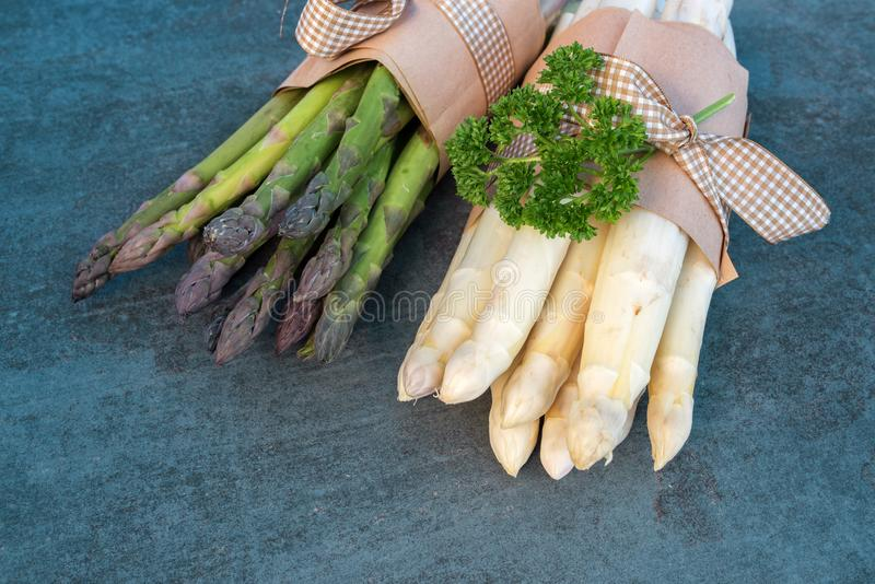 Asparagus bundle with parsley on a stone plate royalty free stock photos