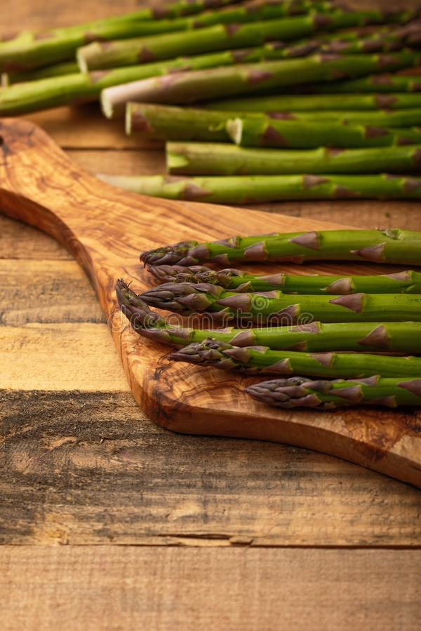 Asparagus on a cutting board. On wooden background. Culinary background. Diet. Delicious and healthy food stock photography