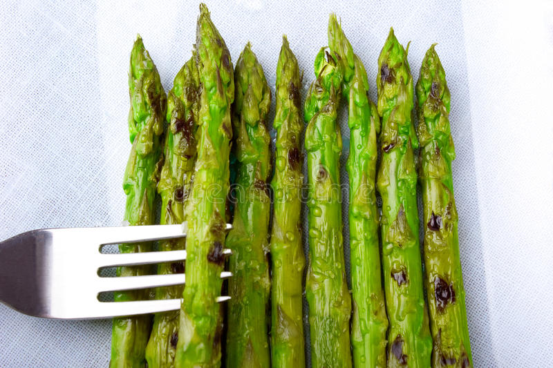 Asparagus with droplets of steam. Asparagus pricked with a fork resting on a glass and rectangular dish full of more asparagus over a linen tablecloth. Droplets stock photo