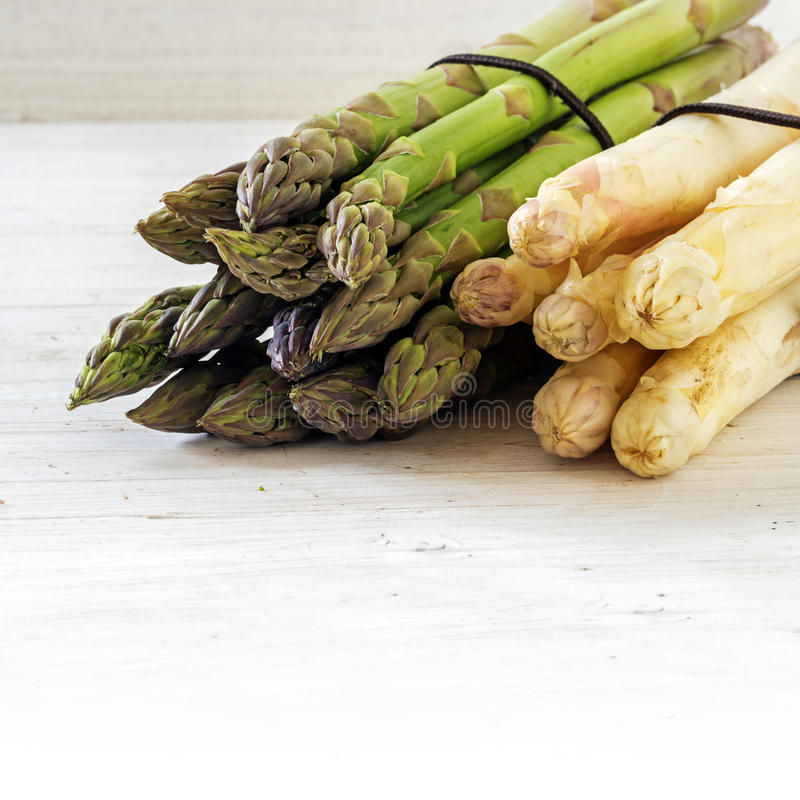 Asparagus, green and white bunch on bright painted wood, background with copy space fades to white, close up royalty free stock photos