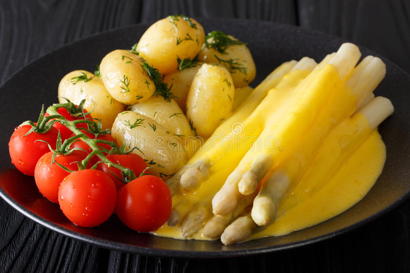 Asparagus with hollandaise sauce, new potatoes, greens and fresh stock photography