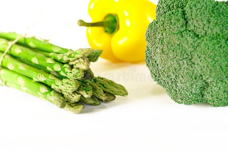 Asparagus, Juicy red and orange peppers with a green tail lies next to Bundle of lettuce and broccoli are on a white background royalty free stock photo