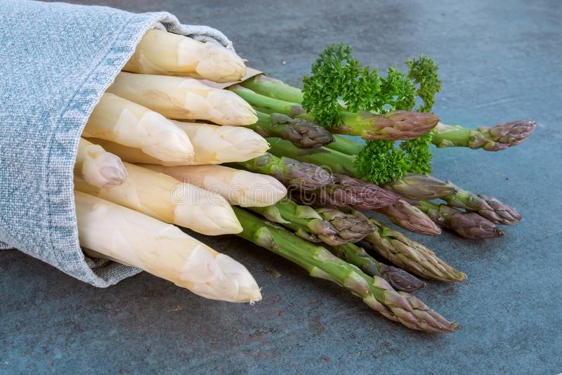 Asparagus with parsley on a stone plate royalty free stock photography