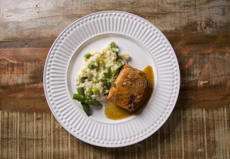 Asparagus risotto with grilled salmon stock photography