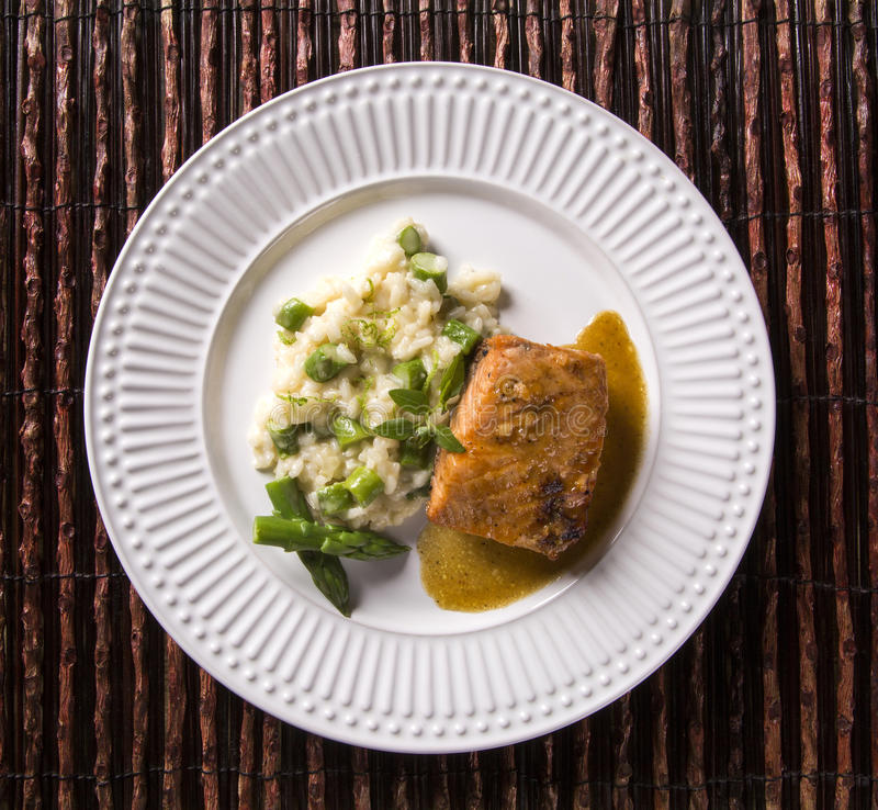Asparagus risotto with grilled salmon stock photo