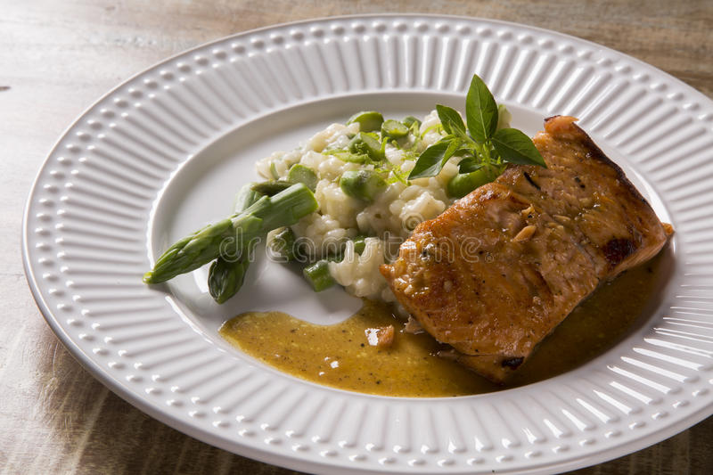 Asparagus risotto with grilled salmon royalty free stock images
