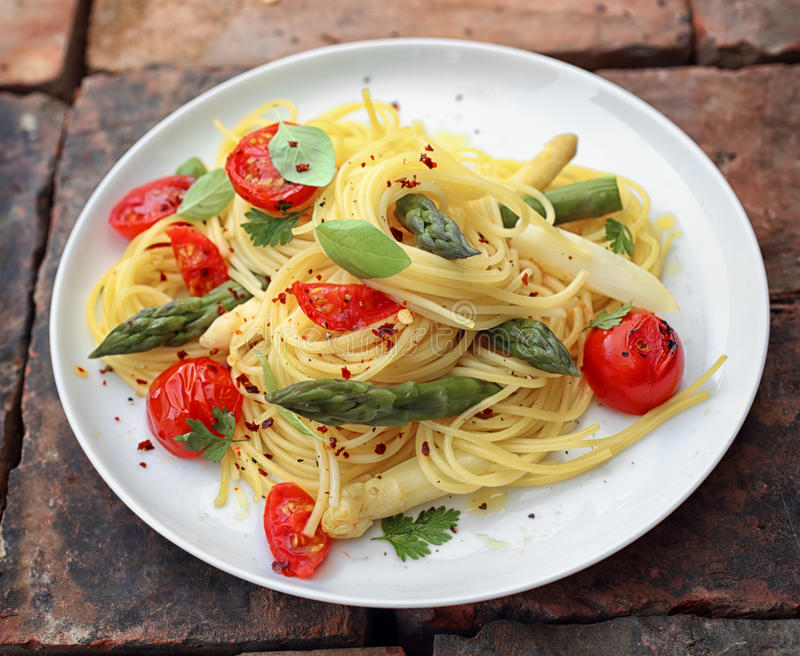 Asparagus spaghetti pasta. With fresh green asparagus shoots, roasted cherry tomatoes and fresh basil seasoned with ground pepper stock photo