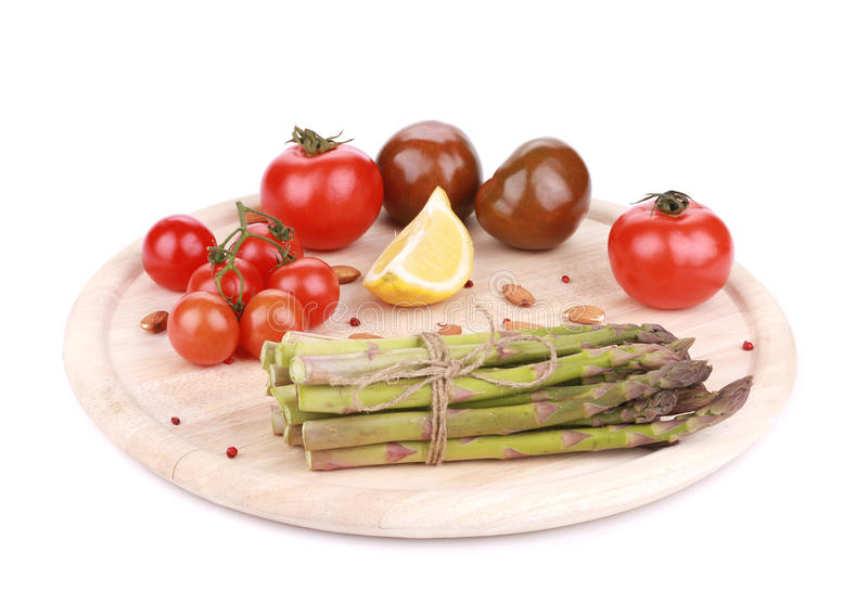 Asparagus and tomatoes on wooden board. stock photography