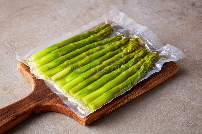 Asparagus vacuum sealed on stone table. Fresh asparagus vacuum sealed ready for sous vide cooking stock photography