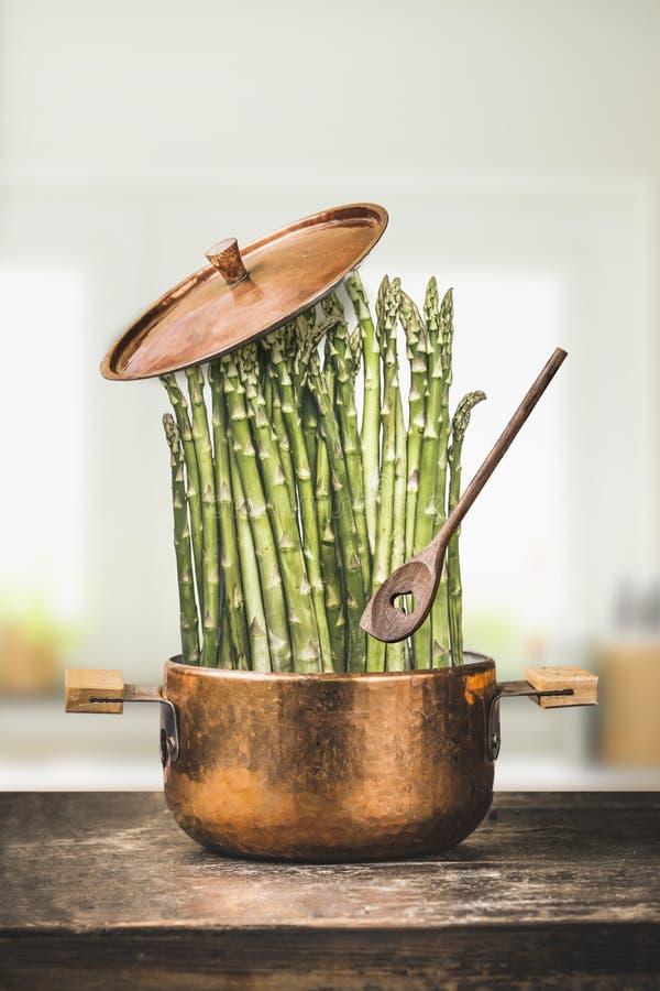 Asparagus w kucharstwo garnku z drewnianą łyżką na nieociosanym kuchennym stole, frontowy widok zdrowe jedzenie wegetarianin obraz stock