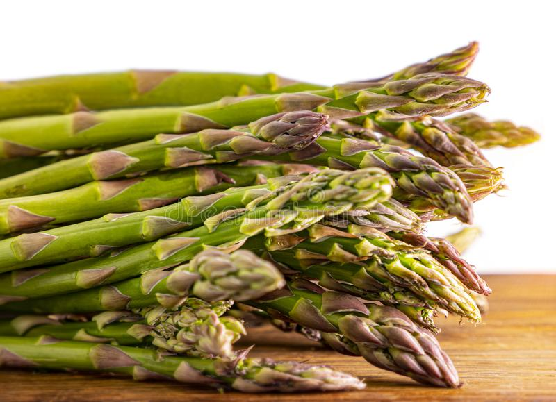 Asparagus on wood, close up. On white stock photography