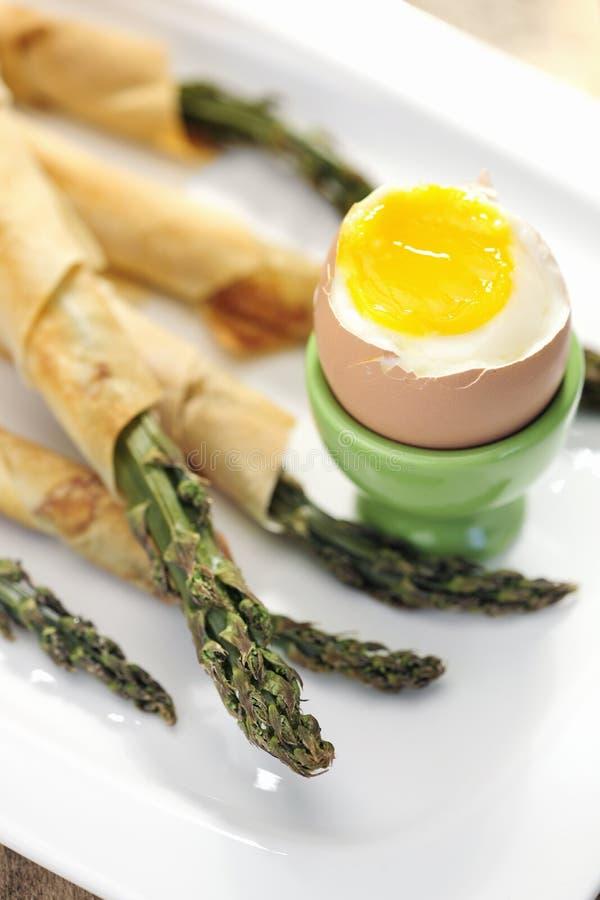 Jedzenie: Asparagus zawijający w cienkim ptysiowym cieście z miękkiej części gotowanym jajkiem zdjęcie stock