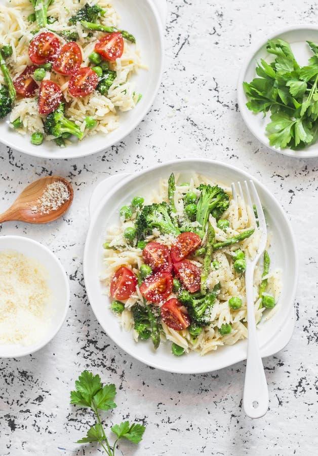 Aspargo, brócolis, ervilhas verdes, massa de creme do orzo com tomates e queijo parmesão Alimento saudável delicioso em um chique imagens de stock