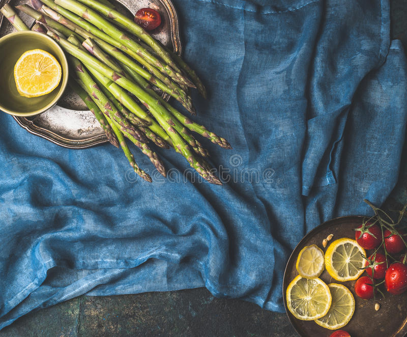 Aspargo e ingredientes do cozimento na obscuridade - fundo azul, vista superior fotografia de stock royalty free