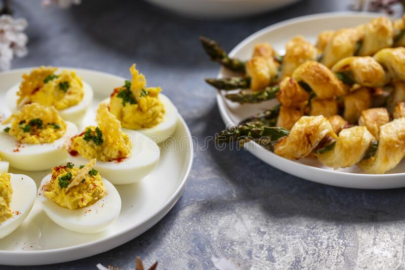 Asparagus in puff pastry and devilled eggs stock photo