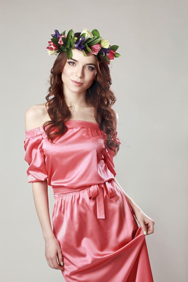 Aspecto romántico apacible de la muchacha con una guirnalda de rosas en su cabeza y un vestido rosado Mujer alegre alegre de la p foto de archivo libre de regalías