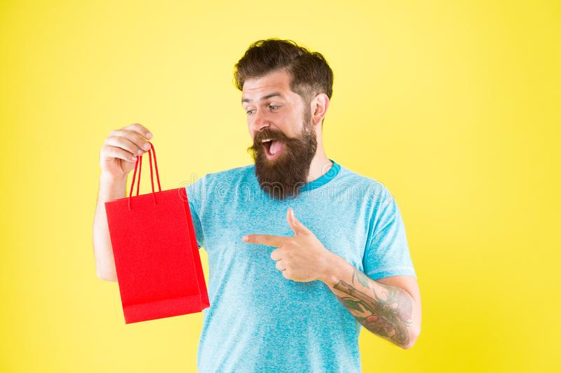 Aspekter kan påverka kundbeslutsfattandeuppförande Lycklig påse för hipsterhållpapper Skäggig man som ler med köpet royaltyfria foton