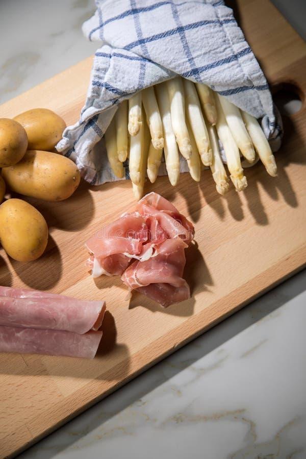 Asperge allemande blanche crue en serviette de cuisine avec du jambon de pommes de terre, faite cuire et fumé sur le fond de con photo libre de droits