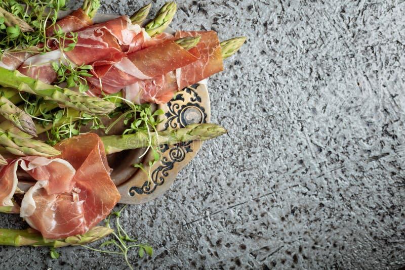 Asperge enveloppée en prosciutto avec de la salade de cresson image stock