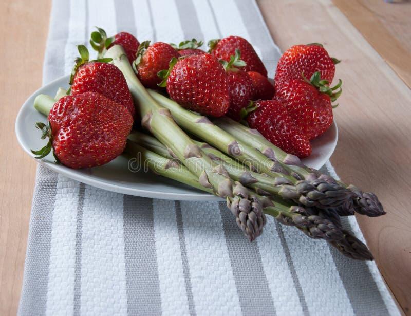 Asperge fraîche avec des fraises du plat blanc Idées pour Orga images stock