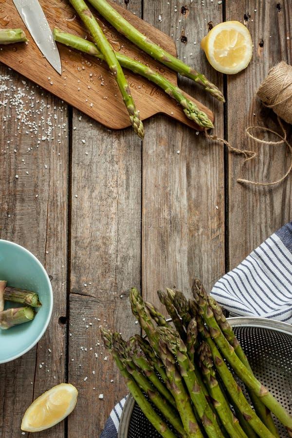 Asperge in landelijke keuken die - op uitstekende houten lijst voorbereidingen treffen te koken stock afbeelding