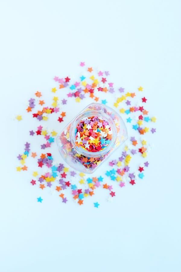 Aspersión coloreada brillante de la confitería de estrellas en un tarro de cristal en un fondo ligero Foco suave, falta de defini foto de archivo