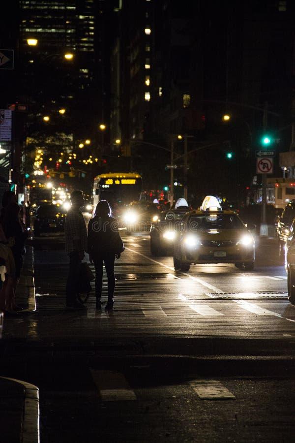 Aspettando un taxi alla notte fotografia stock