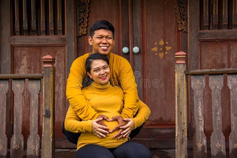 Aspettare asiatico felice della famiglia della campagna il parto, esterno tradizionale della casa immagine stock libera da diritti