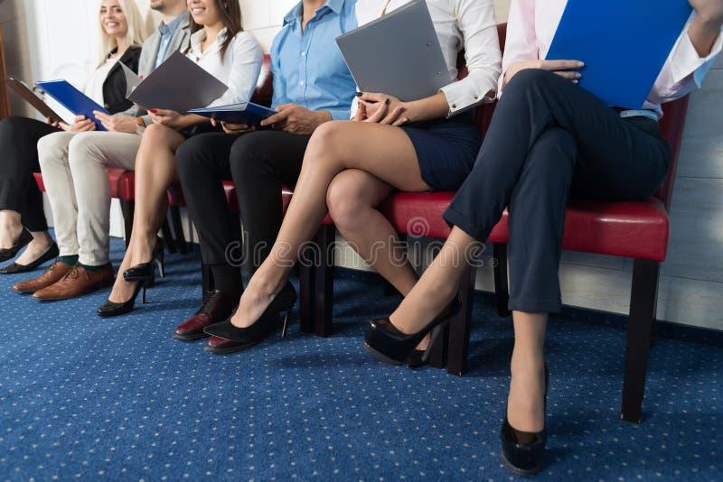 Aspettare dei candidati Job Interview, gente di affari della corsa della miscela che si siede nella linea risorse umane immagine stock libera da diritti