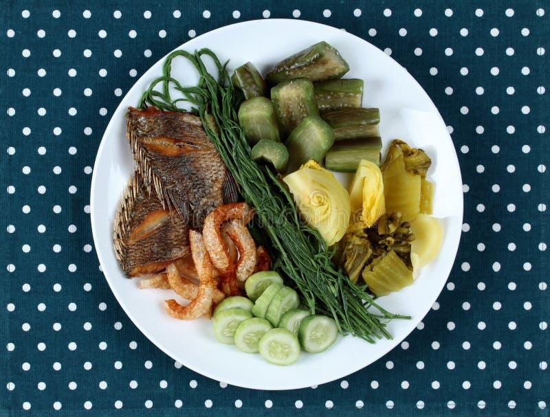 Aspetti il piatto laterale con il pesce infornato di tipalia e la verdura mista immagine stock