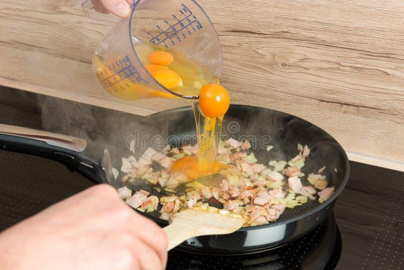 Aspetti per la prima colazione: cottura delle uova rimescolate in una cucina moderna fotografia stock
