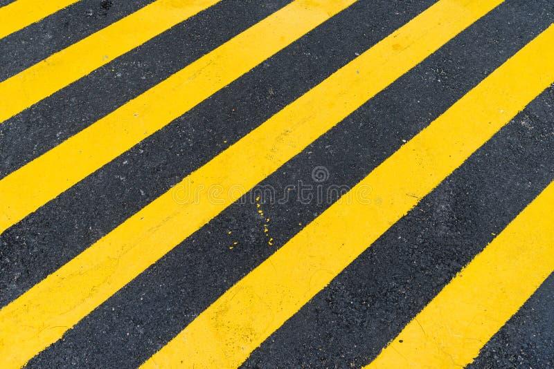 Asphalt Background con la raya amonestadora negra y amarilla diagonal fotos de archivo