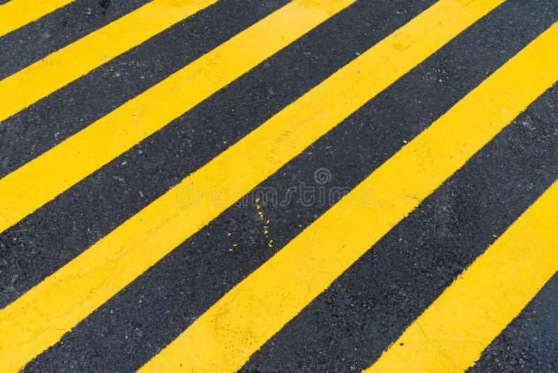 Asphalt Background con la raya amonestadora negra y amarilla diagonal fotos de archivo libres de regalías