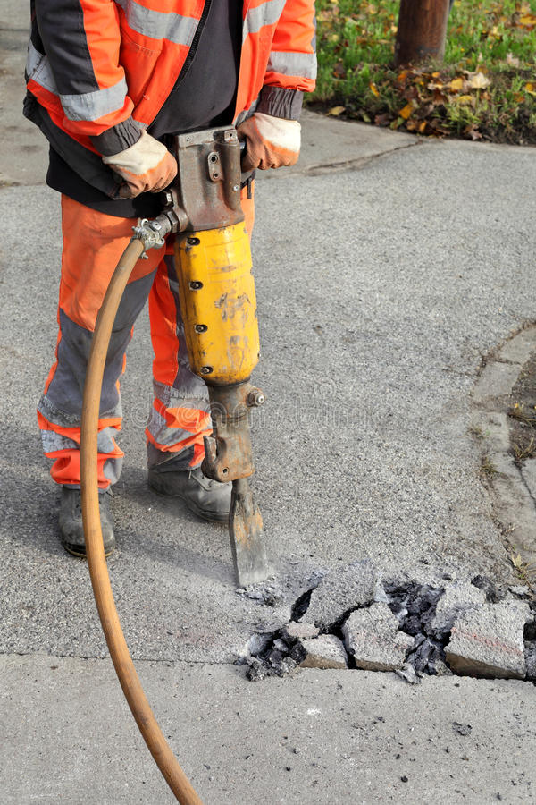 Asphalt demolishing, worker and jackhammer. Worker at construction site demolishing asphalt with pneumatic plugger hammer stock image