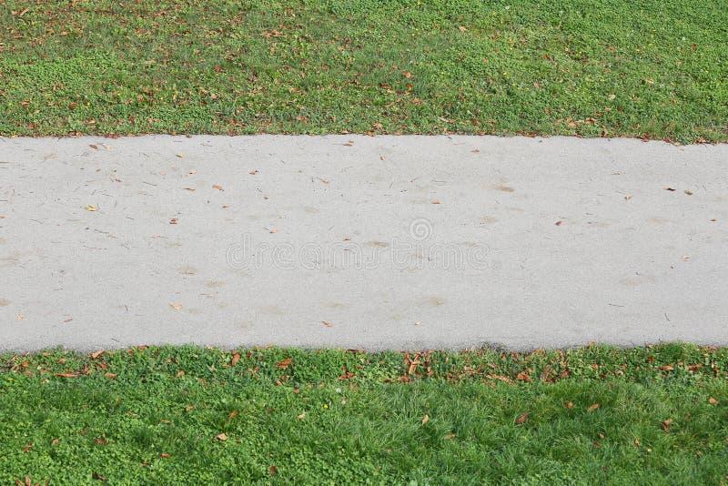 Asphalt Footpath ed erba verde nel lato due immagine stock