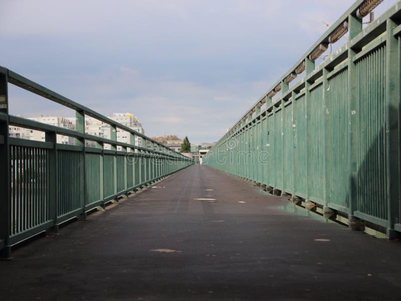 Asphalt Footpath longo com perspectiva verde dos corrimões do metal foto de stock