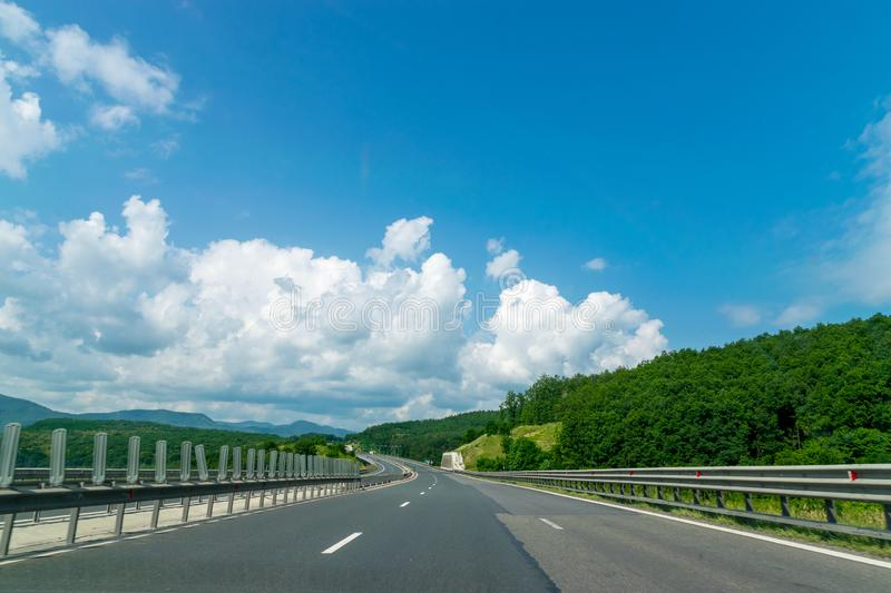 Asphalt highway and green nature landscape on a sunny day with blue sky in Romania stock images