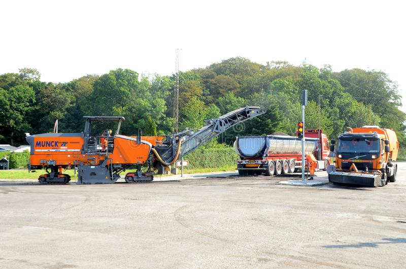 Asphalt milling machine at work in a road crossing. Sonderborg, Denmark - August 27, 2019: Asphalt milling machine at work in a road crossing stock images