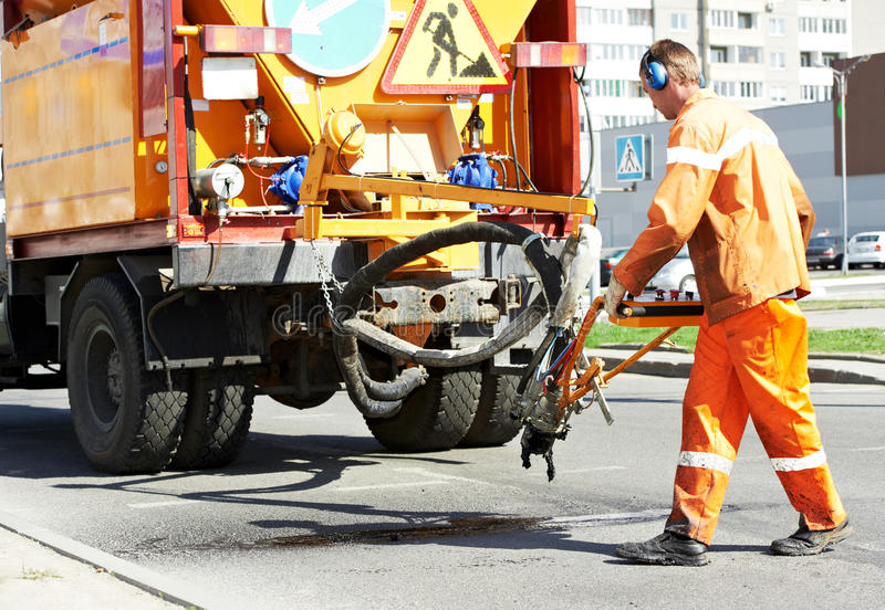 Asphalt patching roadworks. Road worker at asphalt roadway street patching reaparing work stock image