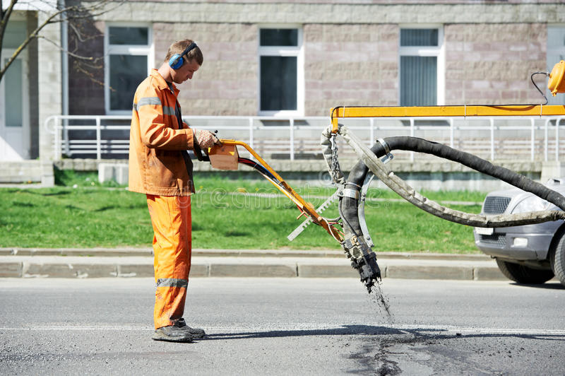 Asphalt patching roadworks. Road worker at asphalt roadway street patching reaparing work royalty free stock image