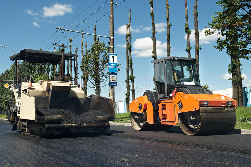 Asphalt pavement machinery at work. Asphalt spreading machine and vibration roller at pavement road works stock photo