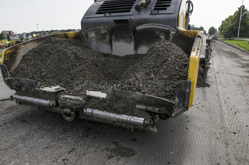 Asphalt paver machine during road construction and repairing works. A paver finisher, asphalt finisher or paving machine. Placing a layer of asphalt. Repaving royalty free stock photo
