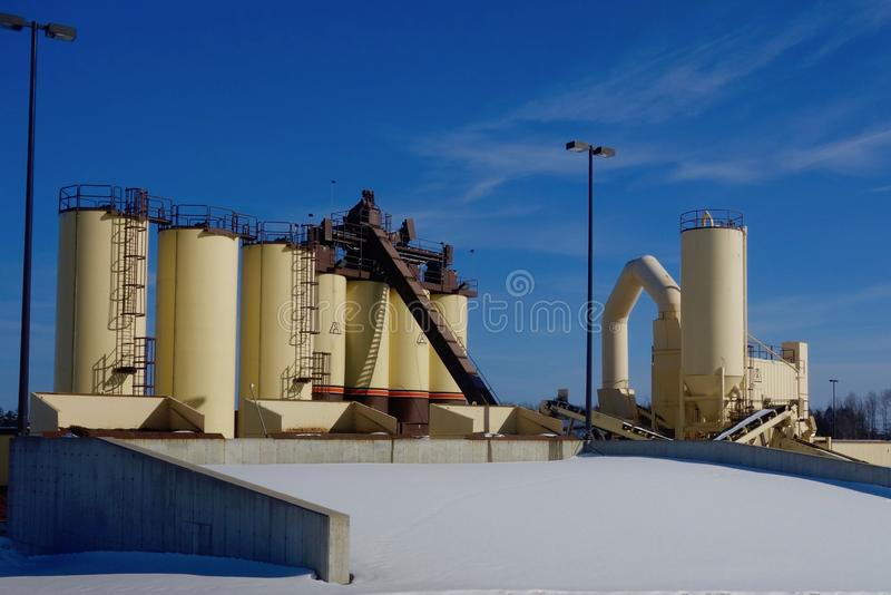 Asphalt production machinery, Cumberland County Maine, March 8, 2019. Blacktop asphalt facility manufacturing yellow towers, deep blue sky, snow, road building stock photos