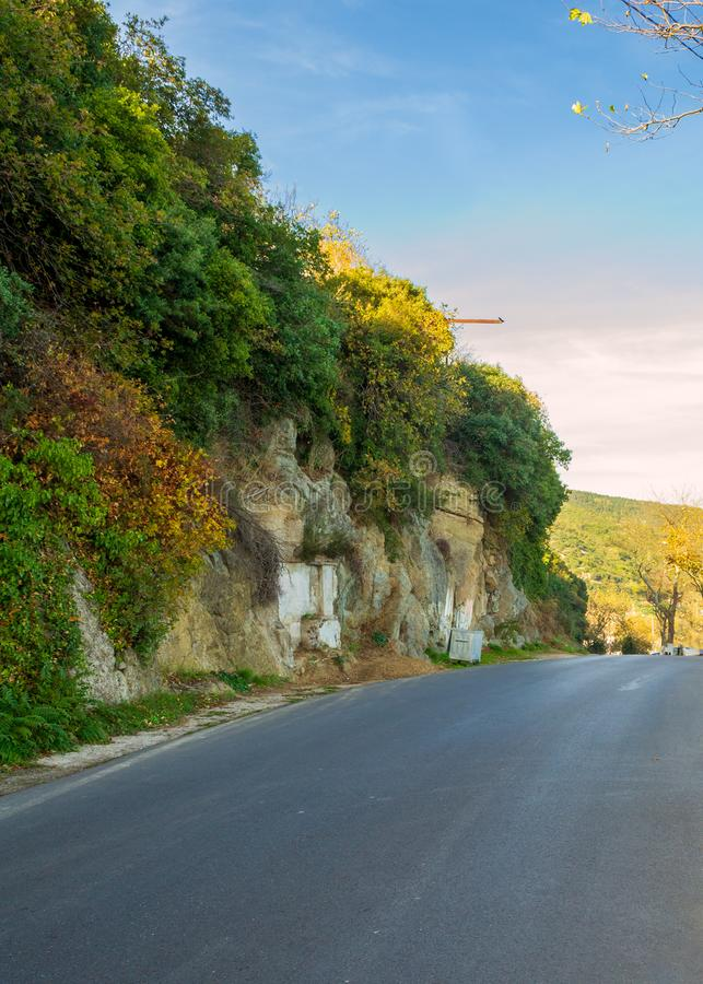 Empty road along stone covered green plant, Sariyer district, Istanbul, Turkey. Asphalt road along mountain wall with green yellow bushes and leaves in bright royalty free stock photography